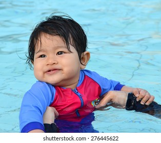 Cute Asian baby girl enjoying and smiling at her first swimming lesson in a swimming pool