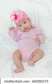 Cute asian baby girl Sit on the bed in pink dress
