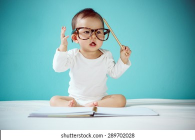 Cute Asian baby girl sitting on the bed in the blue bedroom, Baby healthy and preschool concept