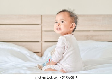 Cute asian baby girl sitting on the bed and playing with a toy bear