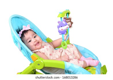 Cute Asian baby girl smiling while playing in her rest chair isolated on white background