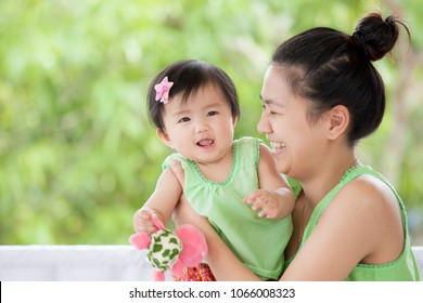 Cute asian baby girl in Thai traditon dress smiling and playing with her mother and turtle doll with love and happiness