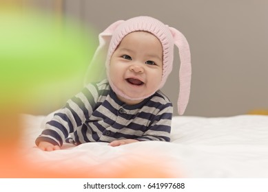 Cute Asian baby girl wearing rabbit hat smiling on the bed