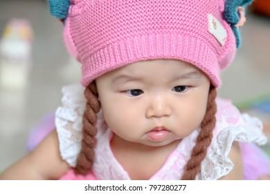 Cute asian baby girl wearing pink hat