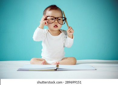 Cute Asian baby girl writing in a book and sitting on bed, Baby healthy and preschool concept