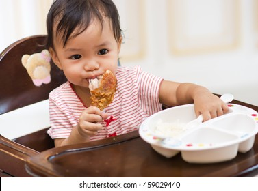 Cute asian baby sit on high chair and eating big fried chicken by herself.Selective focus on child eyes.