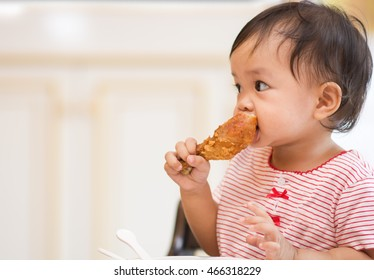 Cute asian baby sit on hight chair and eating big fried chicken by herself
