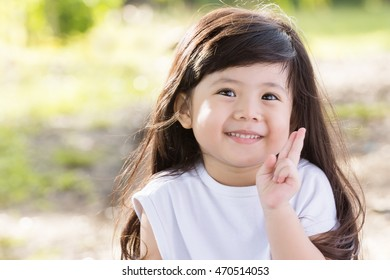 Cute Asian baby Smiling shy in garden Which currently holds the finger.