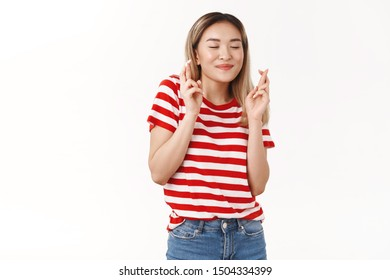 Cute asian blond female student hopes pass all exams making wish close eyes smiling dreamy cross fingers good luck anticipating positive results hopefully praying dream come true white background