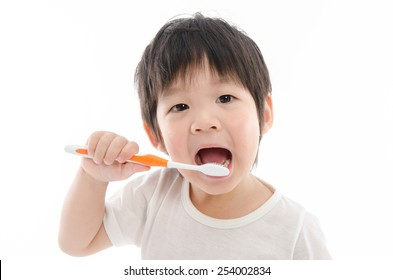 Cute asian boy brushing teeth on white background isolated