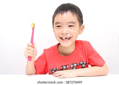 Cute asian boy brushing teeth on white background isolated