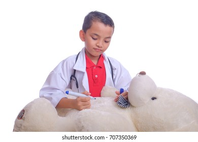 Cute asian boy with coat and stethoscope plays in doctor making operation teddy bear