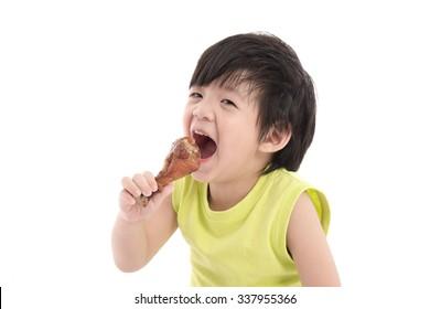 Cute asian boy eating roasted chicken leg
