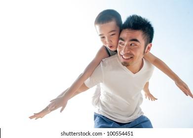 Cute asian boy flying on father