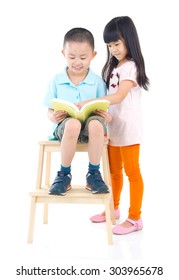 Cute asian boy and girl reading a book