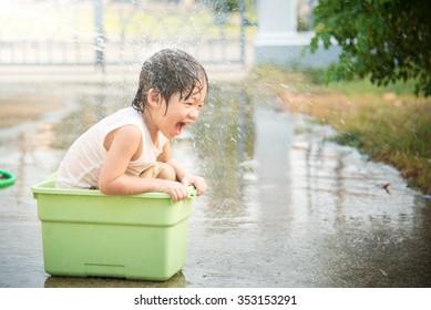 Cute asian boy has fun playing in water from a hose