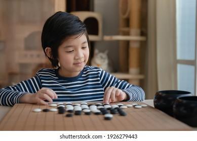 Cute-Asiate-Junge lernte Chinesisch spielen Go-Spiel allein