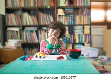 Cute asian boy with long curly hair having art lesson.Homeschooling gifted kid eating in messy classroom.Colorful markers on green table.Mini home library full of books on shelves.Toy blocks cars.