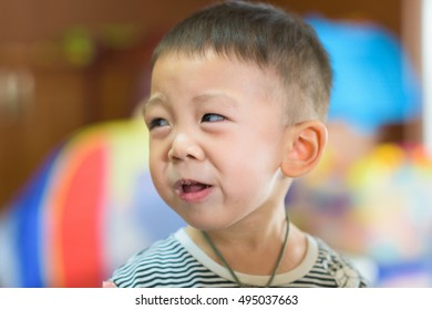 Cute asian boy makes an awful face after tasting a sour tamarin