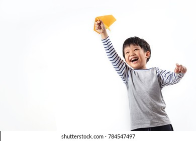 Cute Asian boy playing with paper plane, isolated on white background.
