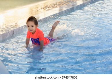 Cute Asian boy playing in swimming pool