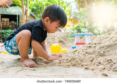 cute asian boy plays with sand on summer day