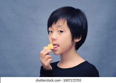 Cute Asian boy posing with a cookie
