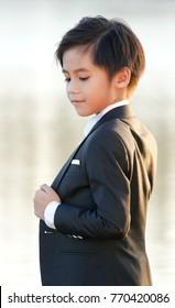 Cute Asian boy wearing suit.