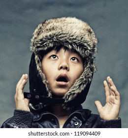 Cute Asian boy wearing winter hat looking surprised