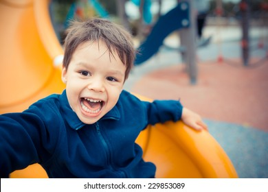 Cute Asian Caucasian mixed race toddler happily playing on a slide in a playground outside in the summer sun