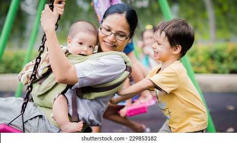 Cute Asian Caucasian mixed race toddler pushing his mother and brother together on a swing in a playground outside in the summer sun