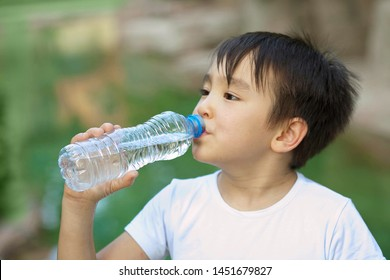 Cute asian child boy drinking clear water outdoors. Pure water