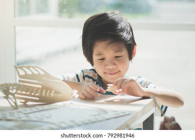 Cute Asian child  builds a toy of wood