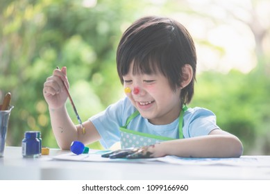 Cute Asian child enjoying arts and crafts painting with his hands