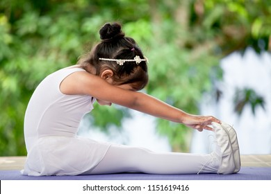 Cute asian child girl doing stretching exercises and practicing a ballet