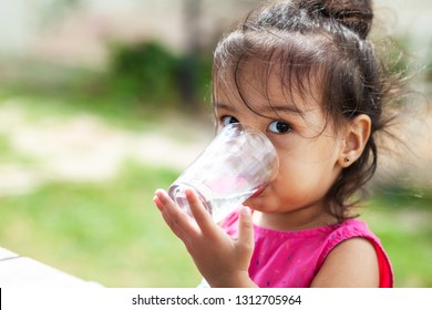 Cute asian child girl drinking clear water outdoors. Pure water