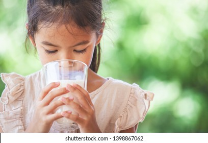 Cute asian child girl is drinking a milk from glass on green nature background