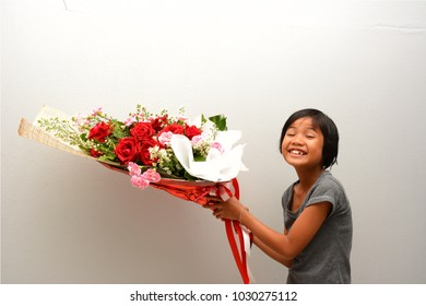 Cute Asian child girl holding flower bouquet in her hands and show pull face of smile. Valentine 's day and mother 's day