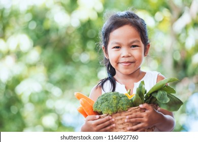Cute asian child girl holding basket of vegetables prepare for cooking with her parent