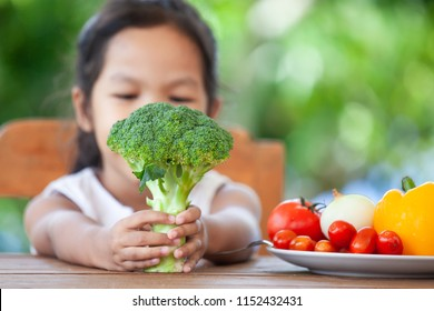 Cute asian child girl holding broccoli and learning about vegetables with happiness