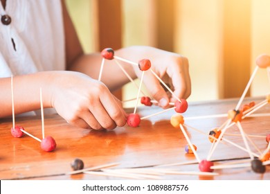 Cute asian child girl playing and creating with play dough and toothpick. Child concentrated with play dough building a molecule model.