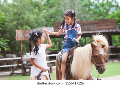 Cute asian child girl riding a pony and making hi five gesture with her elder sister in the farm with fun