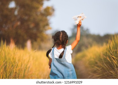 Cute asian child girl running and playing with toy wooden airplane in the field at sunset time with fun