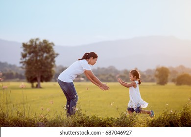 Cute asian child girl running to her mother to give a hug in the field in vintage color tone