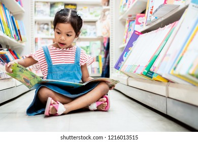 Cute asian child girl select book and reading a book in bookstore in supermarket