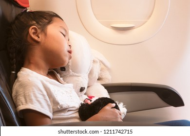 Cute asian child girls traveling by an airplane. She hugging her doll and sleeping  during the flight