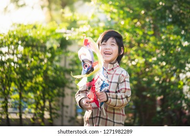 Cute Asian child holding koinobori playing in the park
