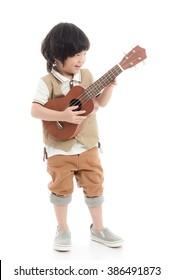 Cute asian child holding ukulele on white background isolated
