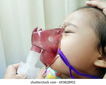 Cute asian child holds a mask vapor inhaler for treatment of asthma on sickbed in hospital. Breathing through a c.
