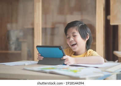 Cute Asian child learning class study online with video call from tablet at home .Social distancing  concept